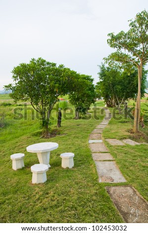 Path of stepping stones leading into lush green garden - stock photo