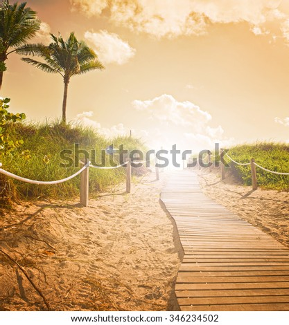 Path on the sand going to the ocean in Miami Beach Florida at sunrise or sunset, beautiful nature landscape, retro instagram filter with flares for vintage looks - stock photo