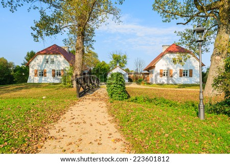 Path over footbridge to traditional cottage houses in rural landscape of Radziejowice village, Poland - stock photo