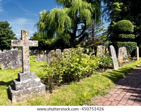 Path through English country churchyard; sunny day in thirteenth century Anglican country church yard  - stock photo