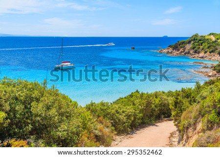 Path to Grande Sperone beach with catamaran boat on sea in distance, Corsica island, France - stock photo