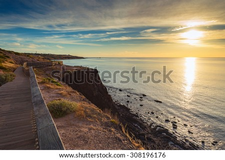 Pathway along the rocky beach at sunset - stock photo