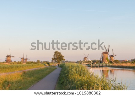 Pathway along water and two rows of windmills during sunset