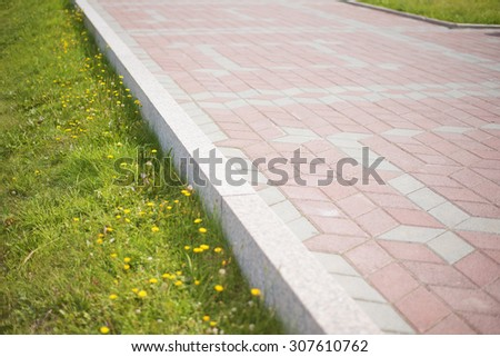 Pathway formed slabs stone between land with fresh green spring or summer grass in a garden park central city town Empty space for full length walking or standing people Yellow spring flowers