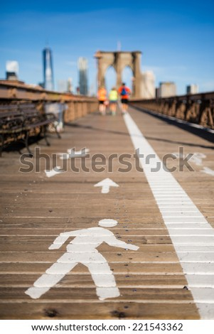 Pathway sign on Brooklyn Bridge with few colorful joggers in the background - stock photo