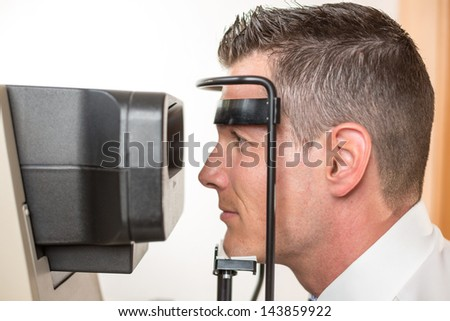Patient and auto refractometer at optician or optometrist for scanning