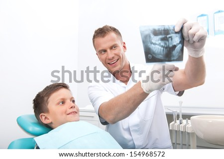 Patient at dentist office. Cheerful little boy sitting at the chair in dental office while doctor showing something at X-ray photo  - stock photo