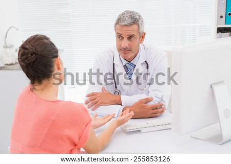 Patient consulting a serious doctor in medical office - stock photo