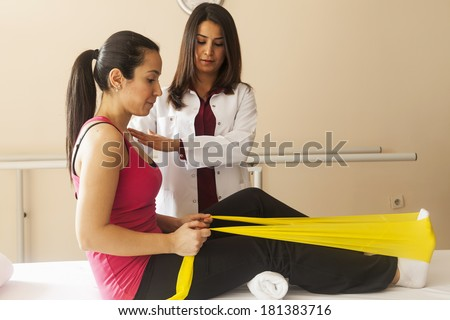 Patient doing some special exercises under supervision of physical therapist - stock photo
