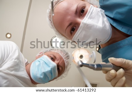 Patient from the dental chair view of the dentist and assistant. - stock photo