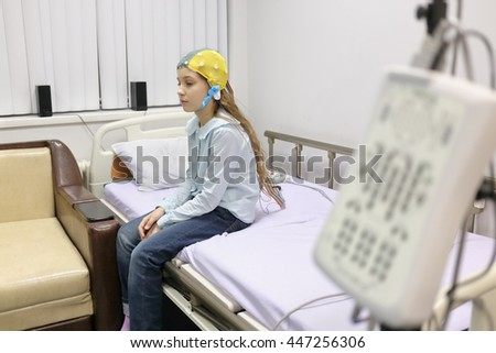 patient girl on procedure of removing of electroencephalogram, sitting on bed looking down - stock photo