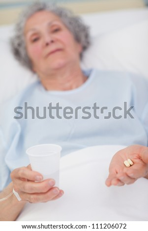 Patient holding drugs and plastic glass in her hands in hospital ward - stock photo