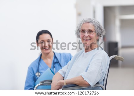 Patient in a wheelchair next to a nurse in hospital ward - stock photo