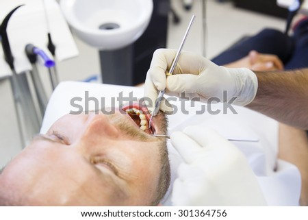 Patient in dental office, having a comprehensive examination done on regular checkup, checking for caries and periodontal disease. Oral hygiene, dental care, preventive procedures concept.  - stock photo