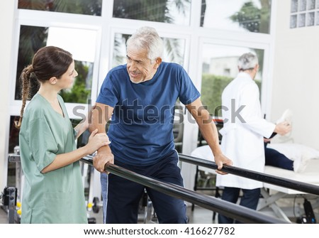 Patient Looking At Female Physiotherapist While Walking Between  - stock photo