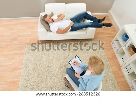 Patient Lying On Couch In Front Of Psychiatrist Writing On Clipboard - stock photo