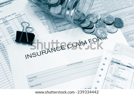 Patient medical bills and claim form with coin jar - stock photo