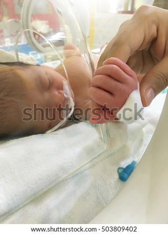 Patient new born baby in incubator at hospital.
