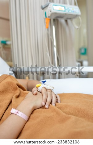Patient on hospital bed, focusing on her hand - stock photo