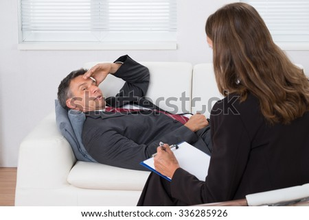 Patient Relaxing On Couch In Front Of A Female Psychiatrist With Clipboard - stock photo