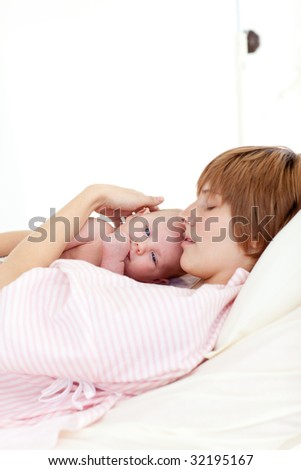 Patient relaxing with her newborn baby in bed in hospital - stock photo