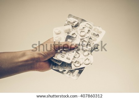 Patient's hand holding a collection of used tablets covers in vintage tone - Drug overuse - drug abuse concept - stock photo