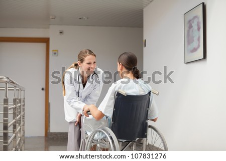 Patient sitting on a wheelchair in front of a doctor in hospital hallway - stock photo