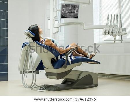 Patient sitting on dental chair wearing dental bib, waiting for her dentist. Dental medicine, dental care, prevention, health concept. - stock photo