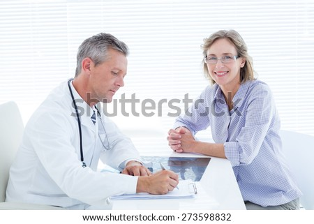 Patient smiling at camera while doctor taking notes in medical office - stock photo