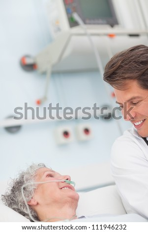 Patient smiling to a doctor in hospital ward - stock photo