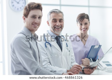 Patient with the doctor and his assistant in the office, they are smiling at camera, healthcare concept