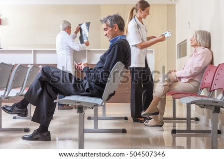 Patients and doctors speaking inside hospital waiting room.