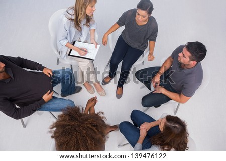 Patients listening to each other in group session sitting in circle - stock photo