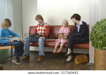 Patients sitting in a waiting room - stock photo