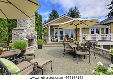Patio area with stone fireplace and concrete floor. Patio table set with umbrella and deck chairs.