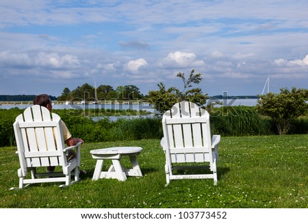 Patio chairs by side of the Chesapeake bay overlooking St Michaels harbor with senior male - stock photo