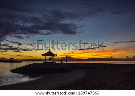 Patio on sand dunes on Bali beach, sunrise. - stock photo