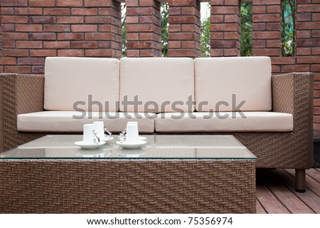 Patio with an outdoor sofa and table against the red brick wall. - stock photo