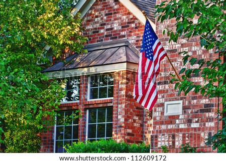 Patriotic American flag in front of southern home - stock photo