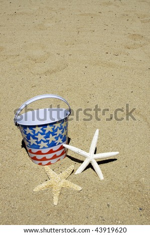 patriotic beach bucket and starfish on sand perfect for cover art - stock photo