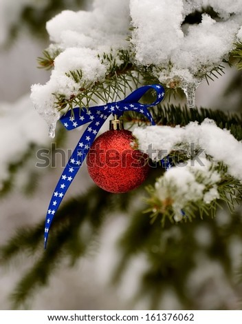 Patriotic Christmas ornament on a snowy pine tree - stock photo