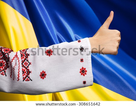 Patriotic concept. Hand of a young woman in the Ukrainian national clothes shows symbol ok with thumbs up against Ukrainian flag background