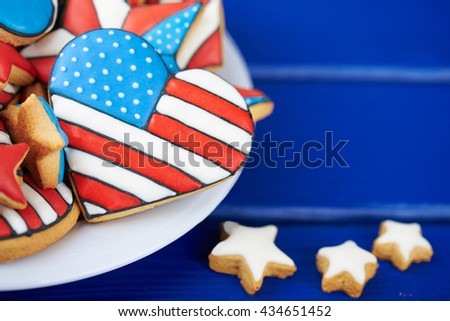 Patriotic cookies for 4th of July on a blue wooden background in a white plate. With scattered stars. Close view - stock photo