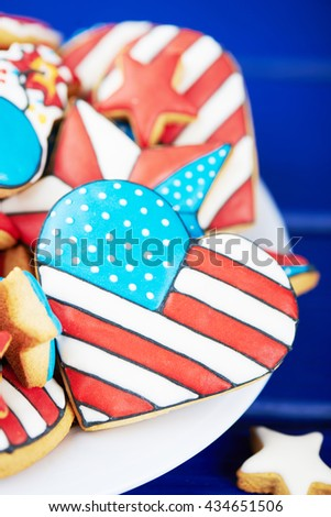 Patriotic cookies for 4th of July on a blue wooden background in a white plate. With scattered stars. Close view. Vertical shot - stock photo