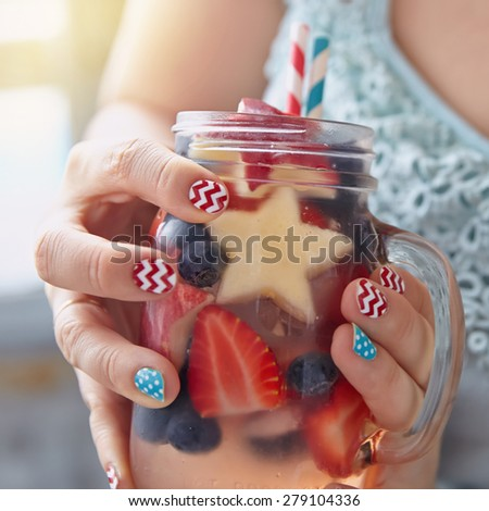 Patriotic drink cocktail with strawberry, blueberry and apple in woman's hands - stock photo