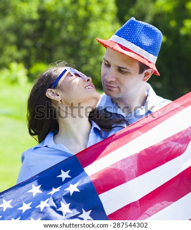 Patriotic holiday cheerful couple with American flag for july 4th.