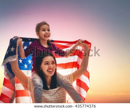 Patriotic holiday. Happy family, mother and her daughter child girl with American flag outdoors. USA celebrate 4th of July. - stock photo