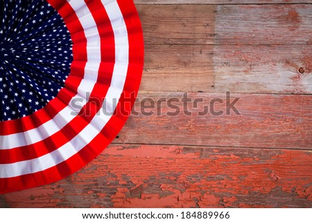 Patriotic Independence Day Badge to celebrate the Fourth of July in the colors of the American flag with stars and stripes on a rustic wooden table with copyspace - stock photo