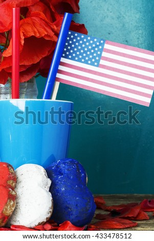 patriotic party. Heart shaped cookies color red, blue, white. cocktail with straws. USA flag and a bouquet of red poppies. celebrating July 4th, or Flag Day