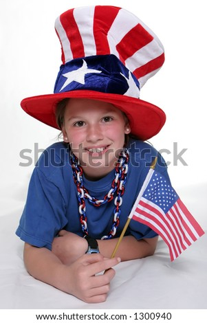 Patriotic young girl laying down with American Flag isolated against a white background.